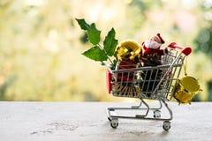 有礼物的购物车或礼物和槲寄生,在bokeh作用背景的霍莉叶子 圣诞节和新年销售概念 免版税图库摄影