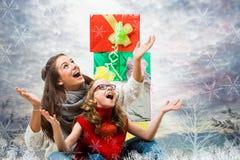 有礼物的逗人喜爱的女孩在雪下 免版税库存照片