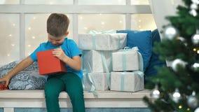 有礼物的逗人喜爱的小男孩开头箱子在圣诞节 影视素材