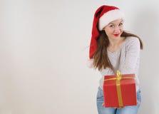 有礼物的逗人喜爱的少妇在白色背景的圣诞老人帽子 图库摄影