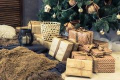 有礼物的金箱子在圣诞树下 免版税库存图片