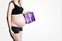 有礼物的年轻白肤金发的孕妇 圣诞前夕、生日或者babyshower礼物 免版税库存图片