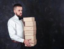 有礼物的年轻滑稽的人为假日19做准备 免版税库存图片