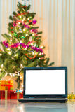 有礼物盒和圣诞灯的膝上型计算机 免版税库存照片