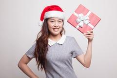 有礼物盒和圣诞老人帽子的年轻亚裔妇女 免版税库存照片