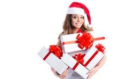 有礼物盒和圣诞老人帽子的激动的逗人喜爱的愉快的年轻白种人十几岁的女孩 免版税库存图片