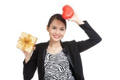 有礼物盒和红色心脏的亚裔女商人 免版税库存照片