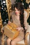 有礼物盒的可爱的相当青少年的女孩在圣诞节backgroun 免版税图库摄影