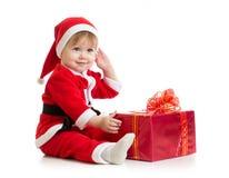 有礼物盒的圣诞节婴孩在圣诞老人的衣服 免版税库存照片