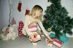 有礼物盒的女孩临近xmas树 免版税库存图片