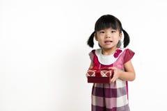 有礼物盒的小亚裔孩子 免版税库存图片