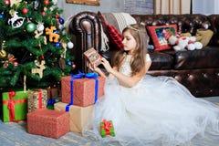 有礼物盒的小女孩在圣诞节内部 库存照片