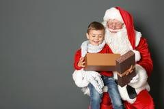 有礼物盒的小男孩坐地道圣诞老人`膝部反对灰色背景 图库摄影