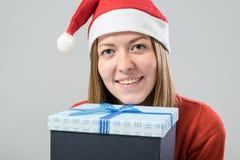 戴有礼物盒的少妇一个圣诞老人帽子 免版税库存照片