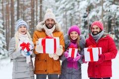 有礼物盒的愉快的朋友在冬天森林里 免版税库存图片