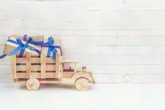 有礼物盒的木玩具卡车在白色木b的后面 免版税库存图片