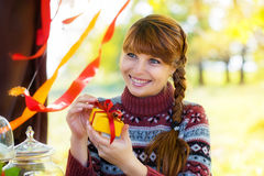 有礼物盒的美丽的女孩在手中在秋天公园 愉快 免版税图库摄影