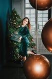 有礼物盒的美女在圣诞树,跳舞附近 免版税图库摄影