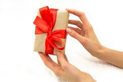 有礼物盒的美好的白种人女性手有红色丝带的 库存图片