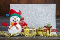 有礼物盒的雪人和圣诞节装饰在被弄脏的银色闪烁卡片的集合 库存照片