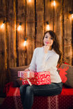 有礼物盒的年轻愉快的美丽的妇女在为圣诞节装饰的墙壁附近坐在房子的屋子里 快活的xmas 免版税库存照片