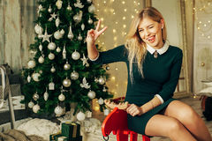 有礼物盒的年轻愉快的美丽的妇女在圣诞树附近坐在房子的屋子里 免版税库存照片