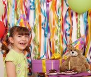 有礼物蛋糕和玩具熊生日聚会的小女孩 免版税库存照片