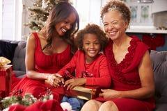 有祖母和母亲开头圣诞节礼物的女孩 库存照片