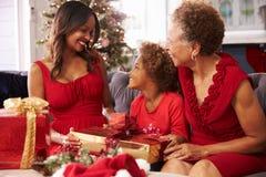 有祖母和母亲开头圣诞节礼物的女孩 库存图片