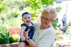 有祖母的逗人喜爱的矮小的女婴在夏日在庭院里 库存图片