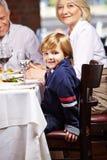 有祖父母的男孩在餐馆 免版税库存图片