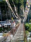 有祷告旗子的桥梁在Marsyangdi河Chame,尼泊尔 免版税库存照片