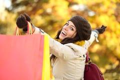有福的妇女购物和有乐趣在秋天 免版税图库摄影