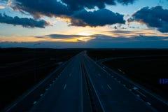 有离开日落的四条车道的柏油路 免版税库存照片