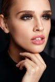 有秀丽面孔、构成和长的黑睫毛的美丽的女孩 免版税库存图片