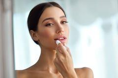 有秀丽面孔的美丽的妇女应用在嘴唇的香脂 应用关心皮肤透明油漆 免版税库存照片