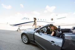 有私人喷气式飞机的妇女下船的汽车 免版税图库摄影