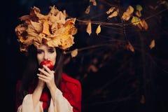 有秋叶冠的妇女吃苹果计算机的 免版税库存图片