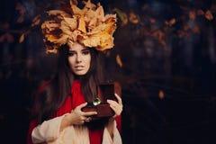 有秋叶冠的妇女有珍宝箱子的 库存照片