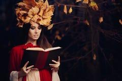 有秋叶冠的妇女读书的 免版税库存图片