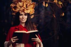 有秋叶冠的妇女读书的 库存图片