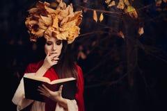 有秋叶冠的妇女读书的 库存照片
