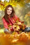 有秋叶在手中和秋天黄色槭树雀鳝的妇女 免版税库存图片
