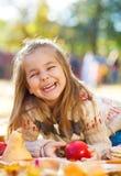 有秋叶的可爱的小女孩在秀丽公园 库存图片