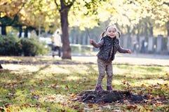 有秋叶的女孩在秀丽公园 免版税库存图片