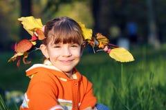 有秋叶的小女孩在头发 免版税库存照片