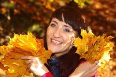 有秋叶的微笑的妇女在现有量 免版税图库摄影