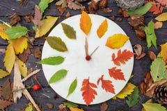 有秋叶的木时钟在黑暗的木背景 免版税库存照片