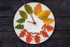 有秋叶的木时钟在黑暗的木背景 免版税库存图片