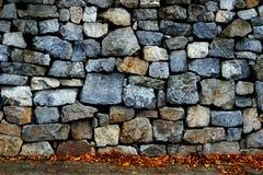 有秋叶的石墙和边路 免版税库存照片